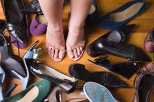 A womans feed amongst lots of shoes