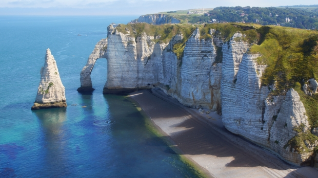 "Étretat in Normandy is renowned for its beautiful cliffs, including three natural arches and the pointed ""needle""."