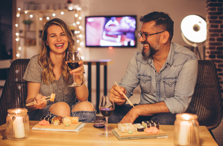 Two mature people laughing as they sit at a table, drinking vine and eating sushi. Evening or night with beautiful yellow lights lightning the scenes. Love is in the air.
