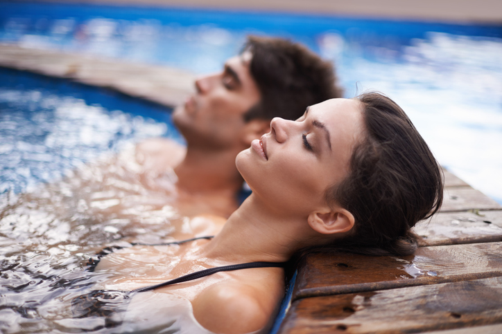 Shot of an attractive young couple relaxing in a pool
