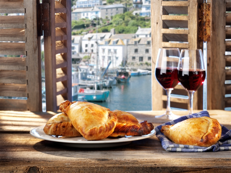 A plate of pasties on a table with red wine and a harbour view behind